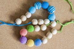 Halskette gemacht von gestrickten Perlen und von Spielwaren f?r das Baby, das in einem Riemen sitzt stockfotografie