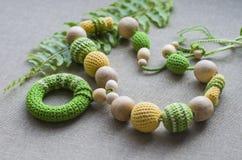 Halskette gemacht von gestrickten Perlen und von Spielwaren f?r das Baby, das in einem Riemen sitzt lizenzfreie stockfotografie