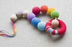 Halskette gemacht von gestrickten Perlen und von Spielwaren f?r das Baby, das in einem Riemen sitzt stockfoto