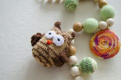 Halskette gemacht von gestrickten Perlen und von Spielwaren für das Baby, das in einem Riemen sitzt Gestrickte Perlen Riemenhalsk stockbild
