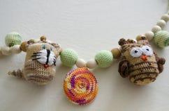Halskette gemacht von gestrickten Perlen und von Spielwaren für das Baby, das in einem Riemen sitzt Gestrickte Perlen Riemenhalsk stockfotografie