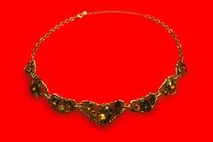 Halskette mit Steinen auf einem roten Hintergrund Lizenzfreie Stockfotos