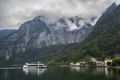 Halstatt, Austria on foggy moody summer day. View of Catholic church in famous Hallstatt alpine village in Austria on shore Hallstätter See lake on moody stock photos