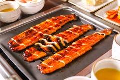 Halstrade ålar på tabellen i restaurang arkivbild