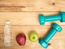 Haltère avec la pomme et bouteille d'eau sur le fond en bois avec c Photo stock