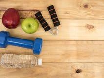 Haltère avec la pomme et bouteille d'eau sur le fond en bois avec l'espace de copie Photos stock