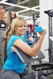 Haltère heureuse d'essais de femme dans la boutique de sport Photos stock