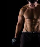 Haltère musculaire intense de fixation d'homme sur le noir photographie stock
