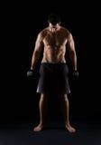 Haltère musculaire intense de fixation d'homme sur le noir images stock