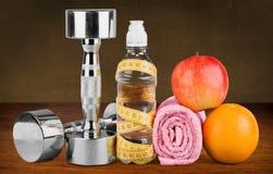 Haltères avec la bande de mesure et les produits sains photo stock