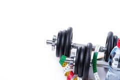 Haltères avec la bande et la bouteille de mesure de l'eau sur le blanc Image stock