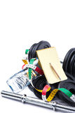 Haltères avec la bande, le bloc-notes et la bouteille de mesure de l'eau sur le blanc Photos stock