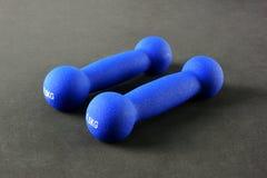 Haltères bleues sur le fond noir photographie stock