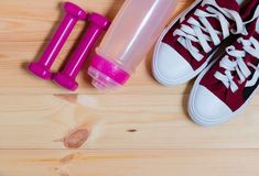 Haltères, bouteille d'eau et espadrilles roses sur le fond en bois Photo stock