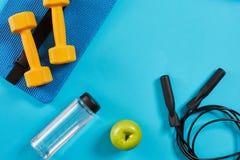Haltères, bouteille de l'eau et corde à sauter sur le fond bleu Vue supérieure Forme physique, sport et concept sain de mode de v Image stock