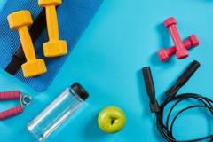 Haltères, bouteille de l'eau et corde à sauter sur le fond bleu Vue supérieure Forme physique, sport et concept sain de mode de v Photographie stock libre de droits