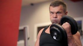 Haltères dans le gymnase - formation de muscle L'homme soulève des haltères dans le gymnase Les grands trains d'homme de Nakachen banque de vidéos
