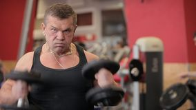 Haltères dans le gymnase - formation de muscle L'homme soulève des haltères dans le gymnase Les grands trains d'homme de Nakachen clips vidéos