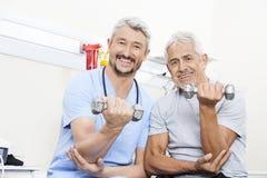 Haltères de levage d'And Senior Patient de physiothérapeute heureux Image libre de droits