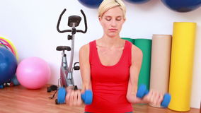 Haltères de levage de femme blonde sur la boule d'exercice banque de vidéos