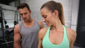 Haltères de levage de femme convenable avec l'entraîneur clips vidéos