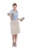 Haltères de levage de femme d'affaires dure regardant l'appareil-photo Photo stock