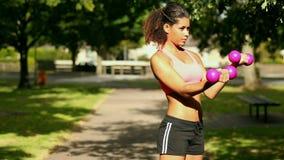 Haltères de levage de femme sportive satisfaite banque de vidéos