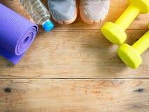 Haltères, espadrilles de sport, bouteille de l'eau et tapis de yoga pour le fitne Photo libre de droits
