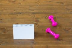 Haltères et carnet roses sur le plancher dans le gymnase Image stock