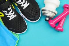Haltères roses, bouteille de sport, serviette et chaussures de course sur le tapis de sport Image stock