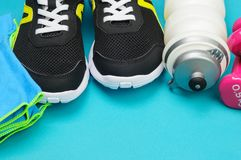 Haltères roses, bouteille de sport, serviette et chaussures de course sur le tapis de sport Photo libre de droits