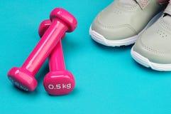 Haltères roses et chaussures de course sur le tapis de sport Photos stock