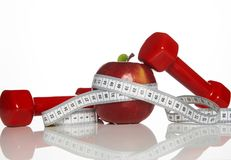 Haltères rouges, bande de mesure de pomme et blanche rouge fraîche Photos libres de droits