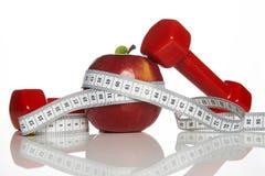 Haltères rouges, bande de mesure de pomme et blanche rouge fraîche Photo stock