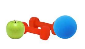 Haltères rouges de forme physique, boule bleue et pomme verte Image libre de droits