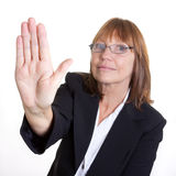 Halt. Older senior business woman's arthritic hand with knobbly fingers in a stop talk to the hand gesture Stock Photos