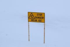 ` Halt, Gefahr! Schwaches Eis ` Zeichen nahe gefrorenem Fluss Lizenzfreie Stockfotos
