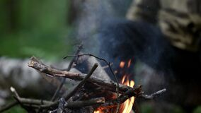 halt in woodland, aged man is resting during trekking in forest, sitting near fire with cup of tea