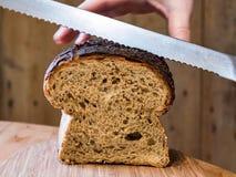 Halten des Getreidespeicher-Brotes beim Schneiden Stockfotografie