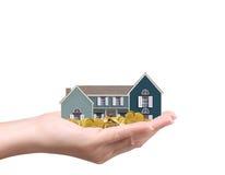 Halten des Hauses und der Münzen Stockbild