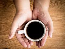 Halten des heißen Tasse Kaffees Stockfoto