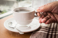 Halten des heißen Tasse Kaffees Lizenzfreies Stockbild