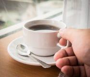 Halten des heißen Tasse Kaffees Stockbild