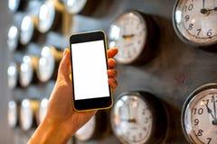 Halten des Telefons mit Uhren auf Hintergrund Lizenzfreie Stockfotografie