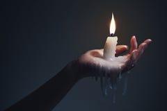 Halten einer Kerze auf einem dunklen Hintergrund lizenzfreies stockfoto