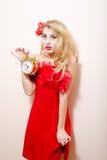 Halten schöner Zauber des Weckers der jungen blonden Pinupfrau im roten Kleid mit Blume in ihrem Haar, das Kamera auf Weiß betrach Stockfoto