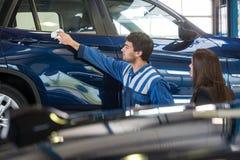 Halten Sie den Mechaniker instand, der einen Kunden zu ihrem Auto zeigt Stockbild