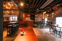 Halten Sie entgegengesetzt und Holztische innerhalb der historischen Brauerei ab, die lokales Bier mit eingetragenem Warenzeichen lizenzfreie stockbilder