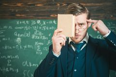 Halten Sie im Verstand Lehrerformelle kleidung und Glasblicke intelligent, Tafelhintergrund getrennte alte Bücher Unrasierte Grif Lizenzfreie Stockfotos