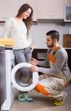Halten Sie Mann nahe Waschmaschine instand stockbilder